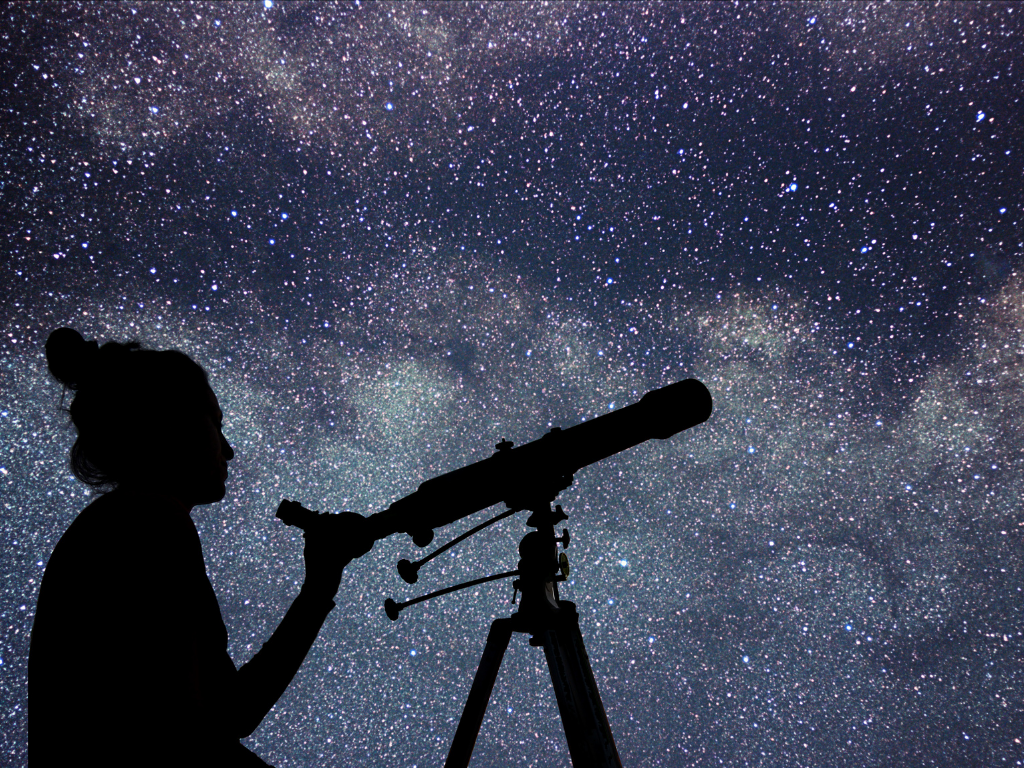 silhouette of a person using a telescope and stargazing