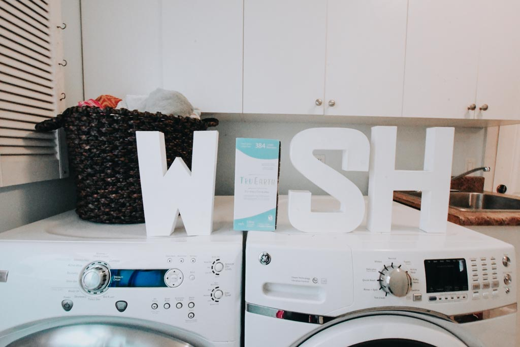 the word wish spelled out with letters and tru earth laundry strips on the top of laundry machines