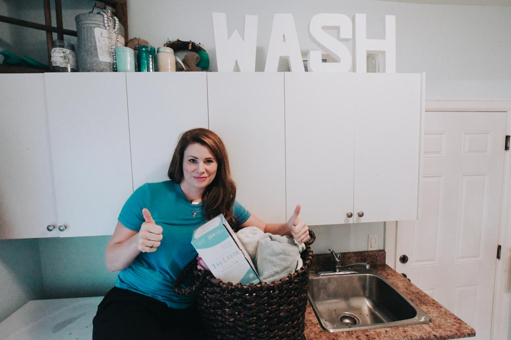woman giving two thumbs up as she sits on her laundry machines with a basket of laundry and tru earth laundry strips beside her