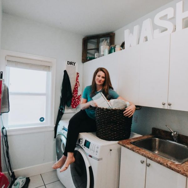 woman sitting on laundry machines with a basket of laundry beside her